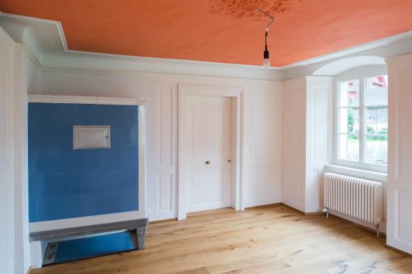 Oranges Zimmer mit historischem Kachelofen  © Fotostudio Fischlin