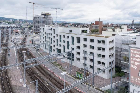 Das Wohnhaus steht am Rande des Gleisfelds und schmiegt sich mit seiner leichten Wölbung daran an. © EM2N