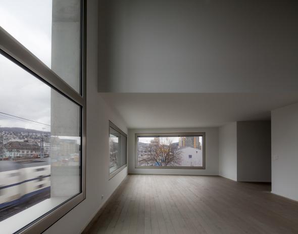 Die Wohnbereiche sind zweigeschossig ausgebildet und öffnen sich über die grossen Fenster dem Gleisfeld zu. Dank schalldichten Fenstern sind die Bewohner dennoch vom Lärm abgegrenzt. © Simon Menges