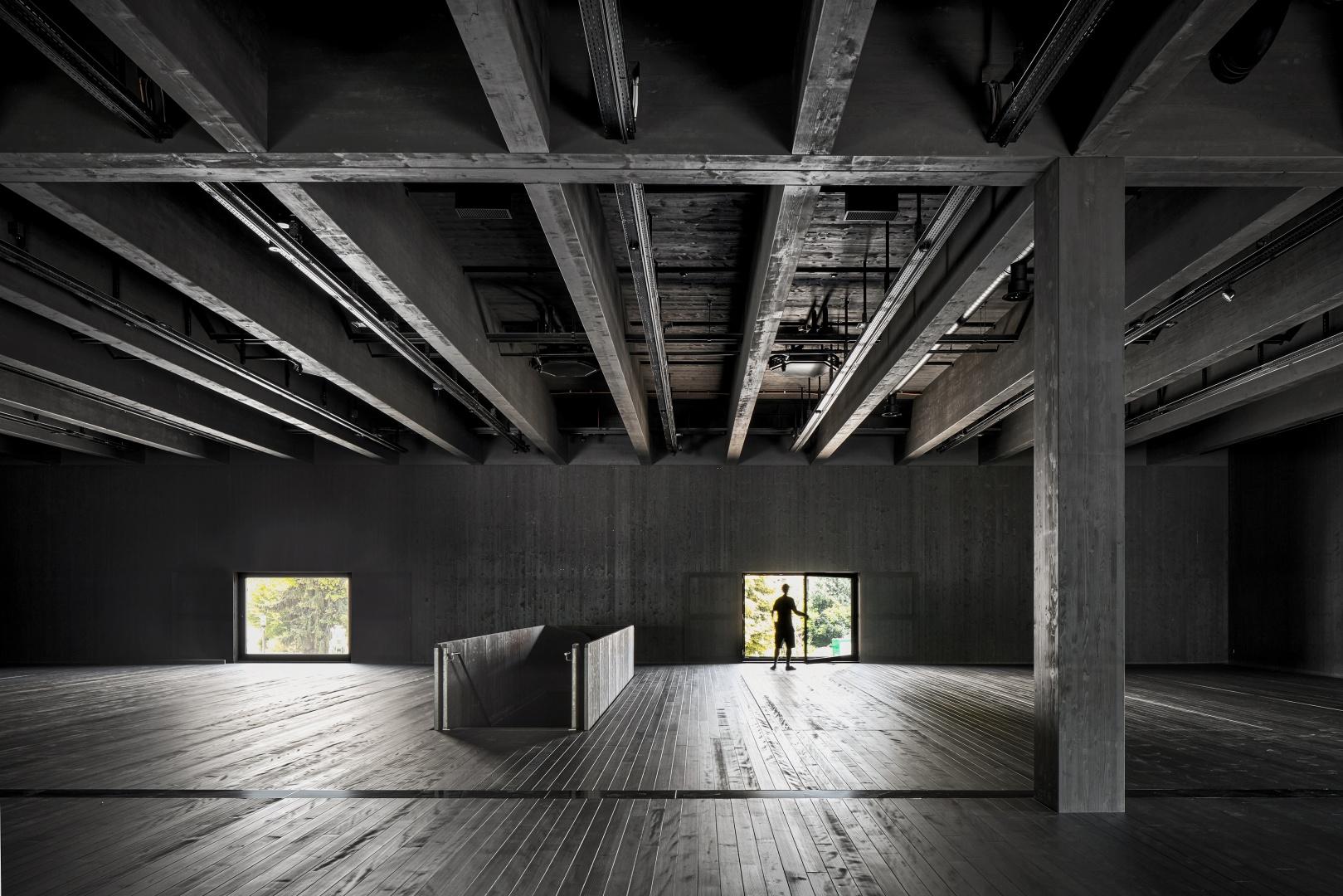 Die räumliche Grundstruktur im Ausstellungsgeschoss (1. OG) ist nahezu stützenfrei. Anthrazitfarbene Tannenriemen spielen mit den gleichfarbenen Wänden  und offenen Balkendecken zusammen. © Ralph Feiner