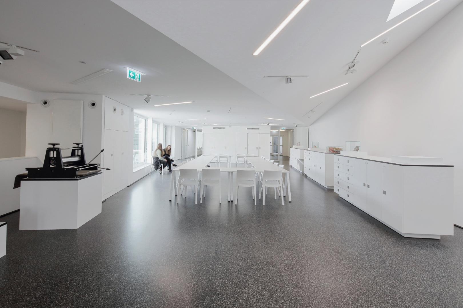 Der Seminarraum im Obergeschoss: Die Glasfassade mündet  auf eine Dachterrasse. Die Kommodenschränke wurden bewusst gewählt, um die Wandschrägen rechts zur Geltung zu bringen. © Usta