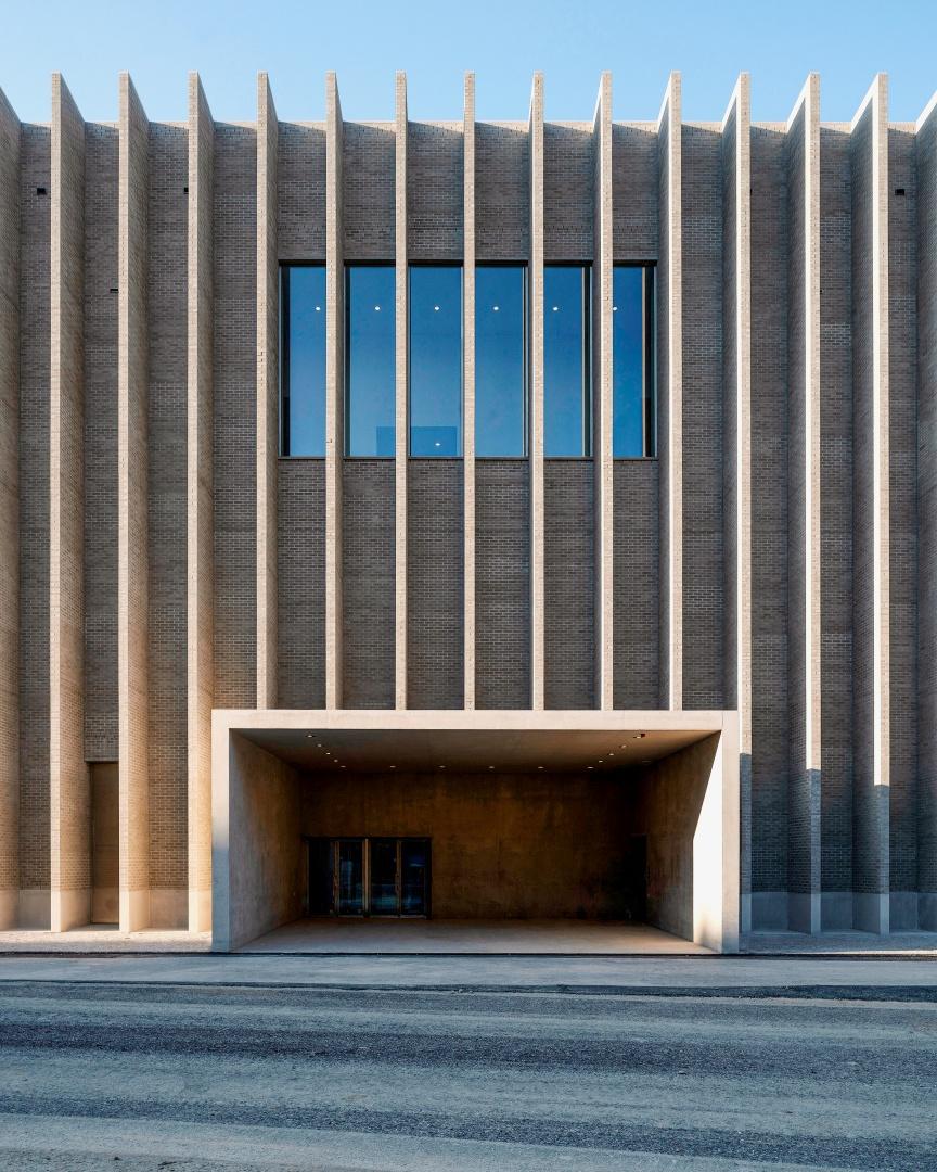 Auf der Platzseite, in der Mitte des nach Mass gebauten Gebäudes, befindet sich der Haupteingang zum Museum. Der Zugang ist proportional zum Gebäude und funktional.  © Matthieu Gafsou