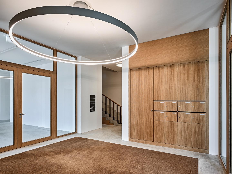 Grosszügiger Eingangsbereich im EG mit anschliessendem Treppenhaus, markant der grosse Ring als Deckenleuchte.  © Roger Frei