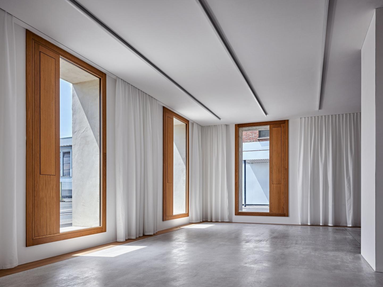 Stirnseitiger Bereich eines Regelgeschosses. Er wird als Sitzungszimmer genutzt, dessen schalldämmenden Vorhänge  zur Behaglichkeit beitragen. © Roger Frei