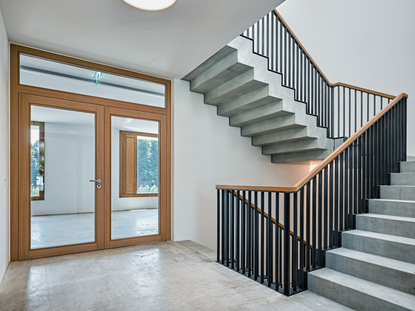 Treppenhaus aus rohem Beton mit einem Geländer aus Stahl und einem Handlauf aus Eichenholz © Roger Frei