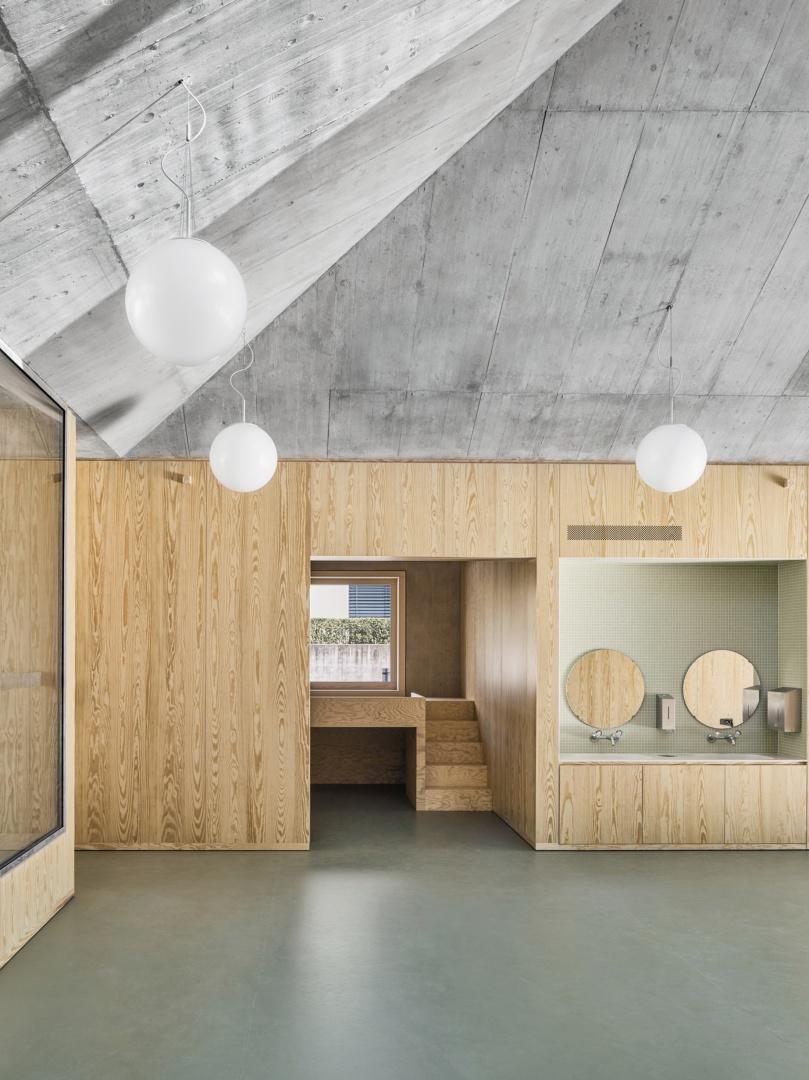 Die Sichtbetondecke des Kindergartens hat eine ähnliche Struktur wie die furnierten Holzeinbauten darunter, welche die Kindergärten voneinander abtrennen.  © Malte Kloes, Christoph Reichen