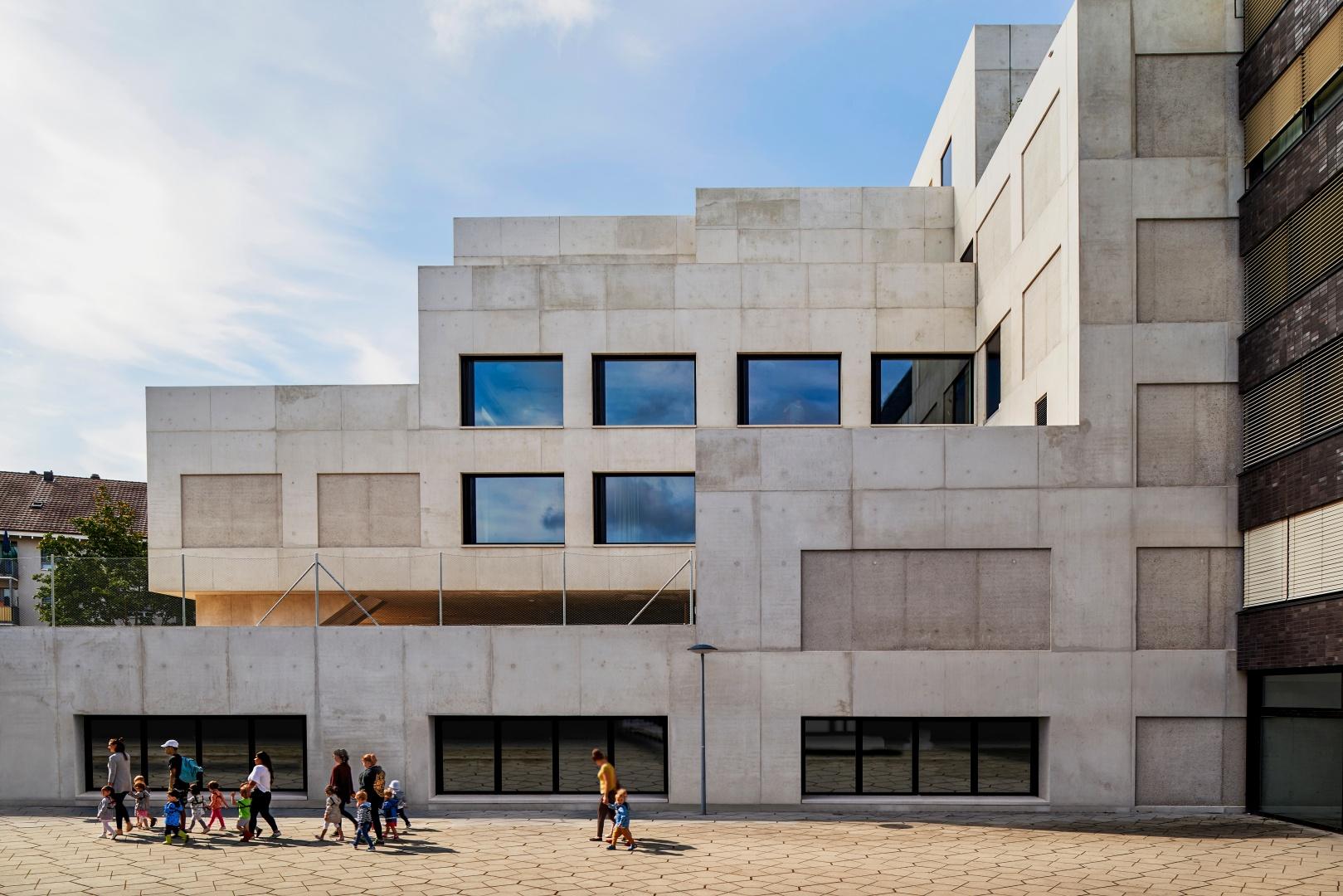 Côté nord du bâtiment de l'école avec des terrasses en gradins qui servent également de zones de récréation. Au niveau du socle, les puits de lumière du gymnase en contre-bas. © Roman Weyeneth