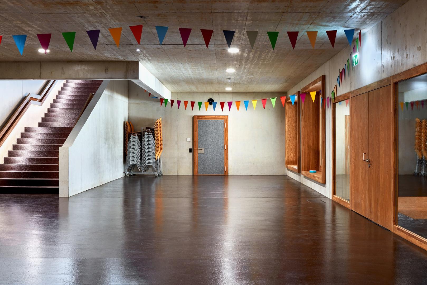 Grand couloir au 1er étage avec de l'asphalte coulé, un concept que l'on retrouve également sur les marches. Les portes et les châssis  de fenêtres en bois de  chêne s'harmonisent au béton brut. © Roman Weyeneth