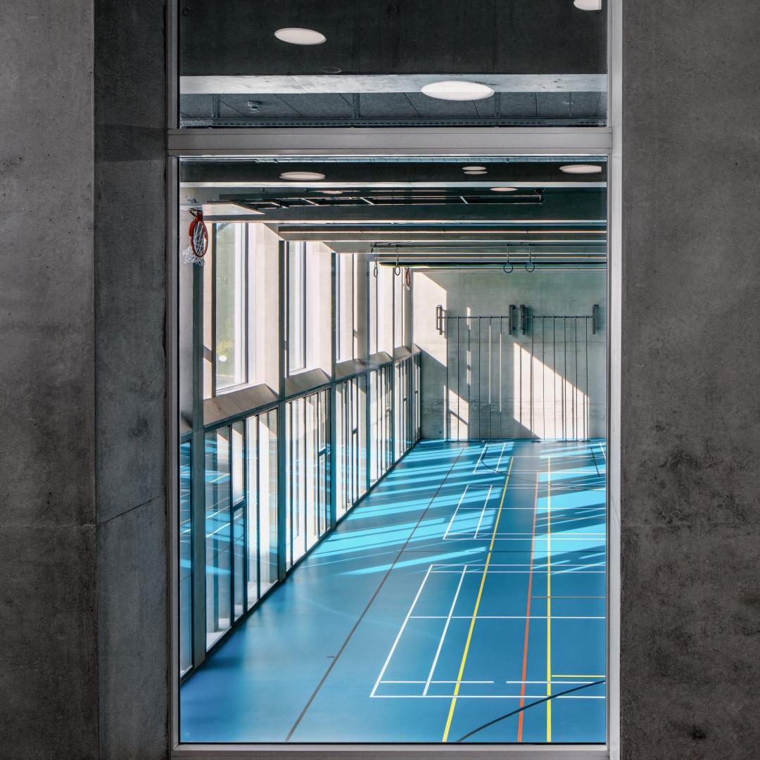 Dans les couloirs, des vitrages sur toute la  hauteur permettent  d'avoir une vue sur les  salles de gymnastique. © yves-andre.ch