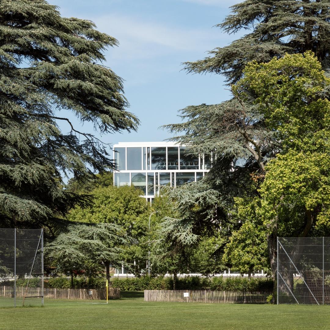 La délicate structure de  la façade du bâtiment  scolaire contraste avec le  vert des arbres séculaires  des anciens jardins. © yves-andre.ch