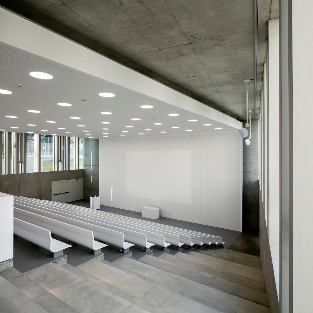 Le minimalisme en  termes de matériaux s'exprime particulièrement bien dans l'aula. Le plafond acoustique se prolonge  sur le mur et devient une surface de projection.  © yves-andre.ch