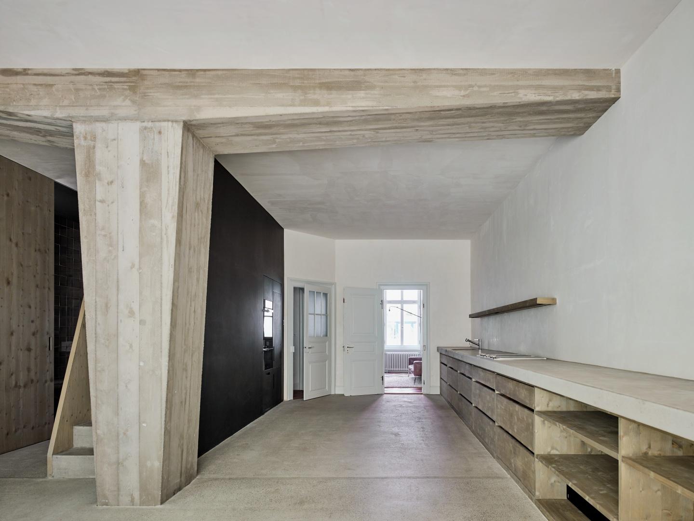 La grande cuisine-salle de séjour au rez-de-chaussée  est en béton brut: la colonne avec solive qui ouvre l'espace de la pièce se trouve sur la chape de ciment.  © Beer Merz Architekten