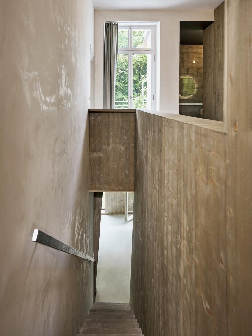 Vue du 1er étage sur l'escalier étroit, à droite,  l'habillage en bois, recouvert d'un glacis vert olive. © Beer Merz Architekten