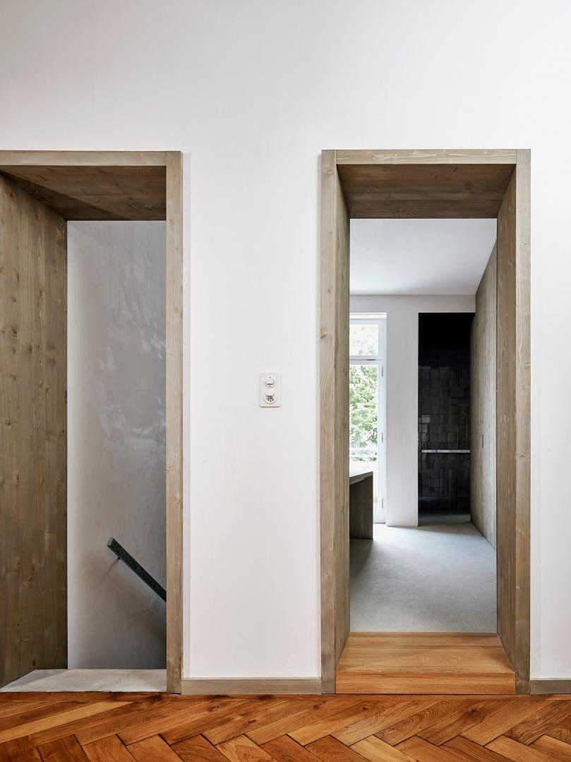 Treppenaufgang und Durchgang zum Badezimmer  sind mit tiefen Laibungen aus lasiertem Holz gerahmt. © Beer Merz Architekten
