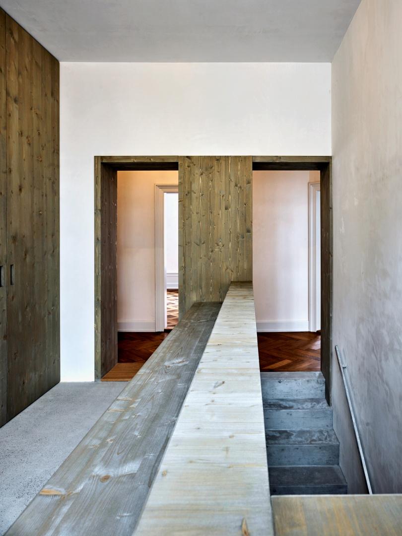 Symmetrie der Durchgänge beim Treppenaufgang und  Flur Richtung Badezimmer. Die Schrankwand entlang des  Gangs hat gegenüberliegend  eine Ablagefläche. © Beer Merz Architekten