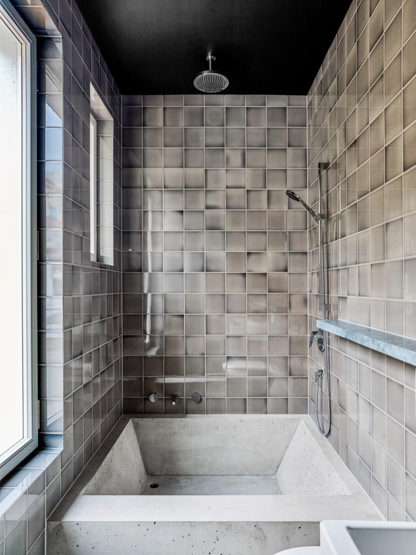 les carreaux de salle  de bain du fournisseur «Golem» brillent de reflets nacrées grâce  à leur structure de glacis craquelé. La baignoire à mi-hauteur, coulée dans du béton sur place, a été rendue hydrophobe. © Beer Merz Architekten
