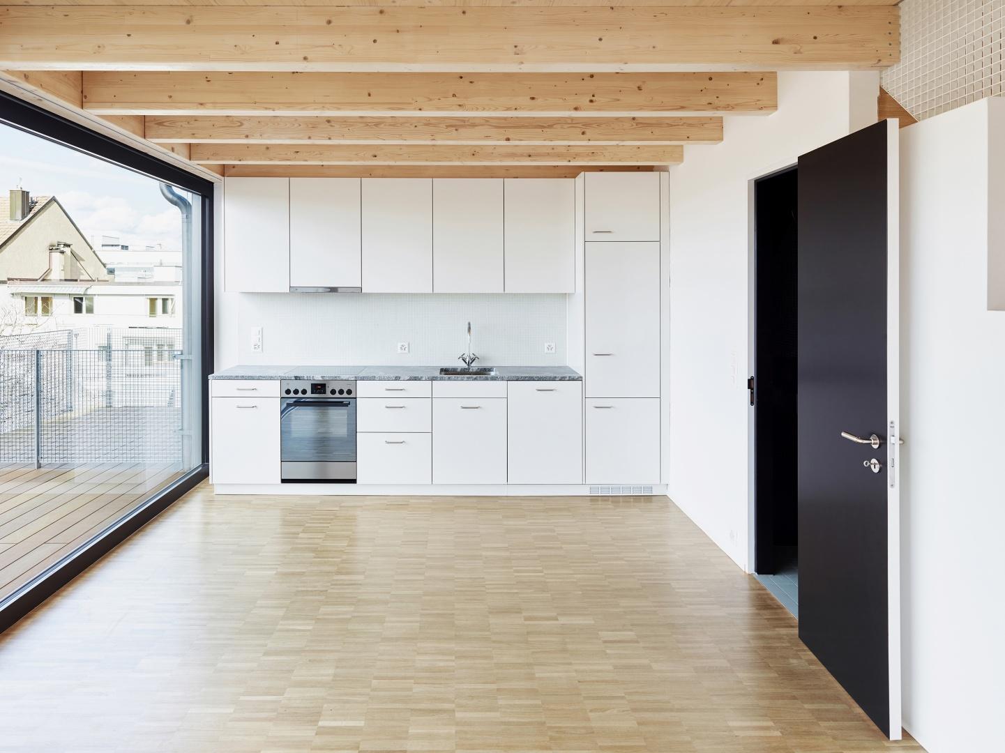 Die Deckenbalken des unteren Wohngeschosses sind von den beiden Firstpfetten abgehängt.  Die Unterteilungen der Hebefenster nehmen  die Fluchten der Deckenbalken auf. © Lukas Räber