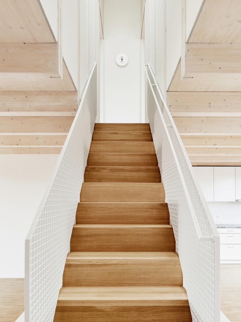 Les deux appartements en  duplex sont conçus comme  des contreparties, réalisées en  bois de construction, lasurées  en différentes teintes (glacis blanchâtre et couleur bois naturel). © Lukas Räber
