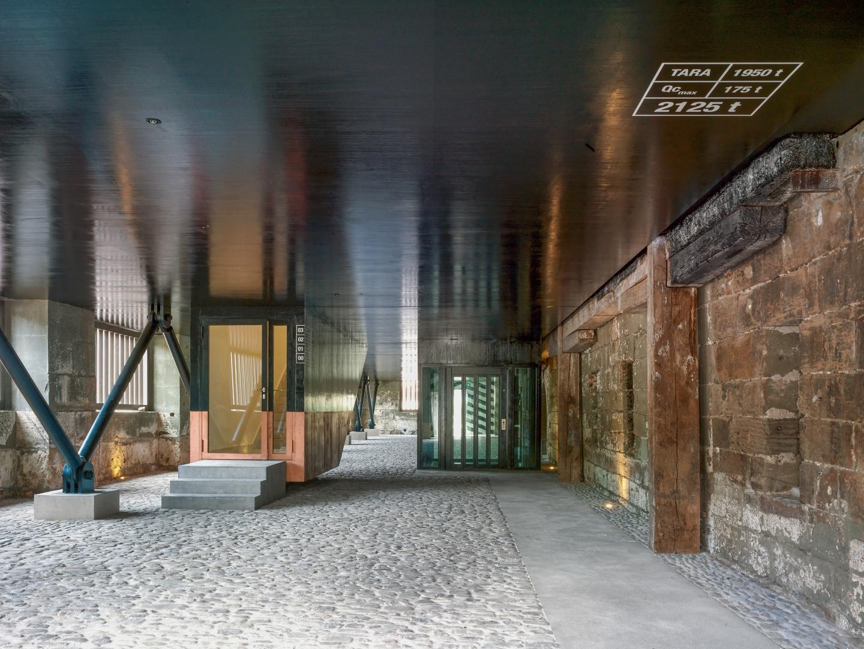 Der Zugang zum Gebäude  erfolgt durch eine kleine Holztür. Wie bei einem Frachtschiff,  wird dieser von einer Reihe von V-förmigen Stützen Metall getragen. © Werkhof
