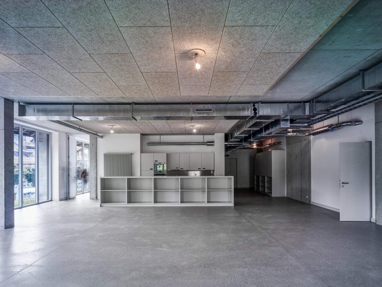 Im ersten Stock befindet  sich das Quartierzentrum.  Bei Bedarf steht ein Gemeinschaftssaal mit massgeschneiderten Möbeln aus MDF zur Verfügung.  Der Unterboden besteht  aus geschliffenem Beton. © Werkhof