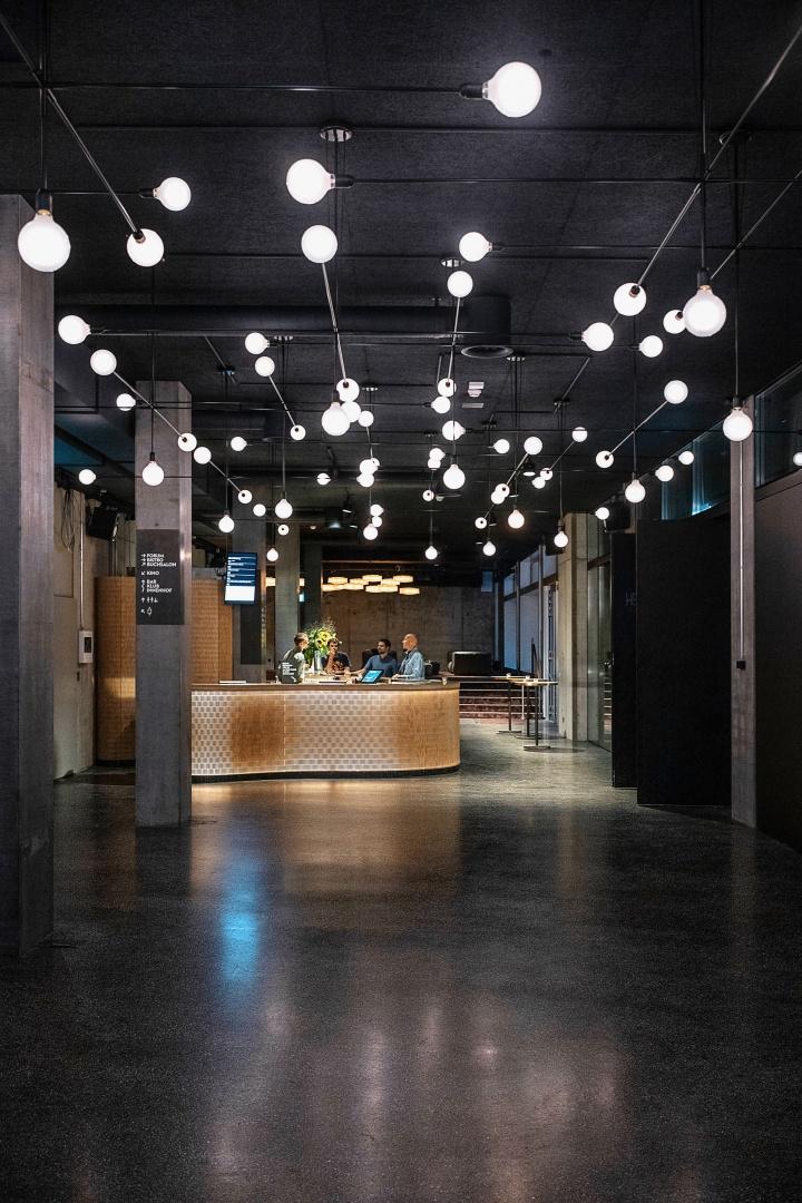 Lichter: Foyerbereich im Erdgeschoss mit rückwärtigem Klub und Bartheke. Die kosmos-spezifische Leuchte «Mobile» strahlt durch alle Räume. Die filigrane, modulare Lichtstruktur mit ihren LED-Lichtpunkten lässt einen Sternenhimmel entstehen. © Burkhard & Lüthi