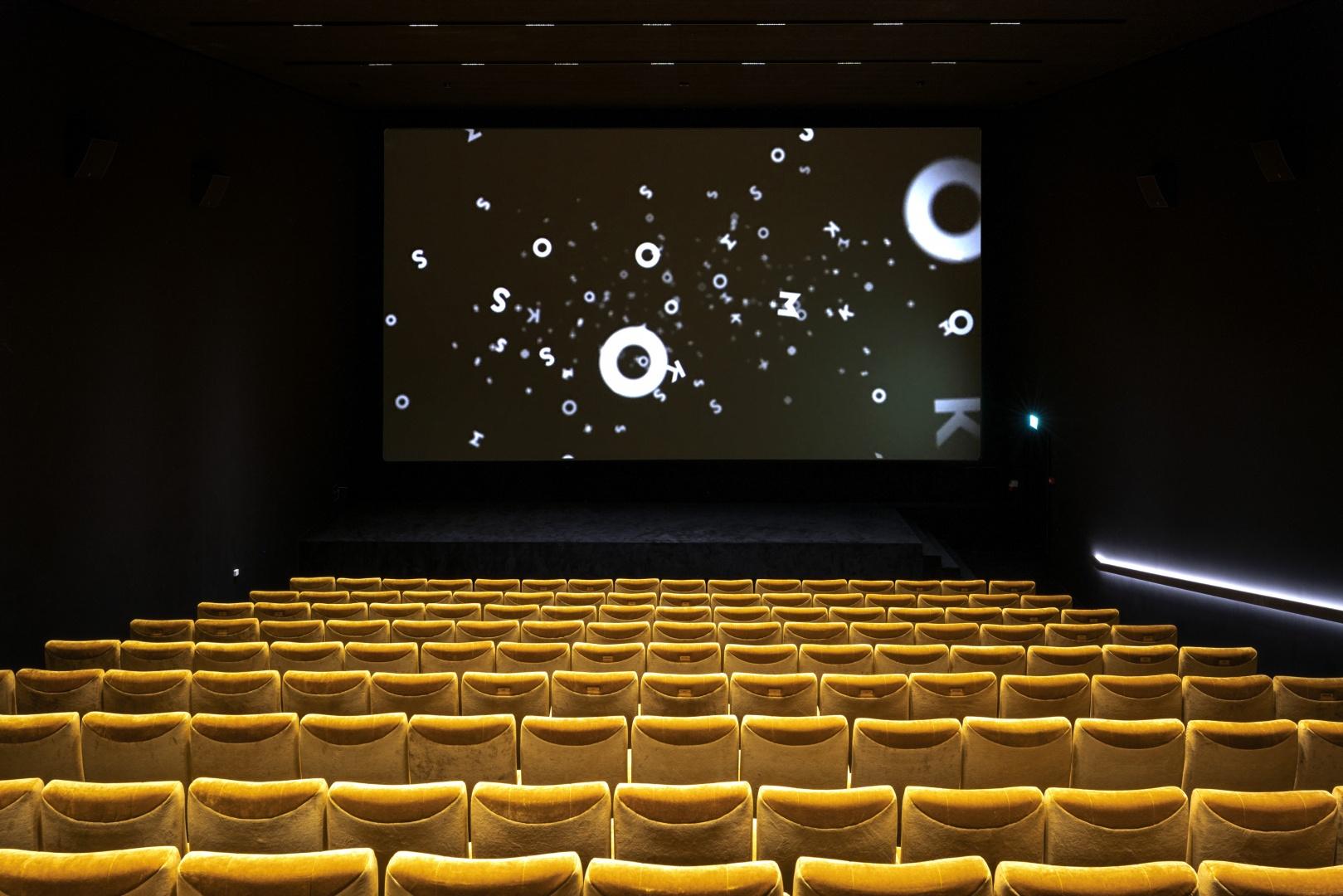 Die sechs unterschiedlich grossen Kinosäle sind  ganz in schwarz gehüllt;  für den optimalen Sicht-  und Sitzkomfort sorgen die goldfarbenen Sessel. © Burkhard & Lüthi