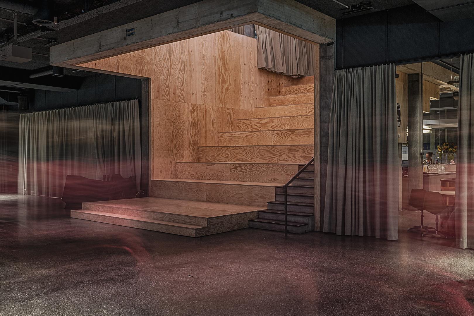 Treppe: Blick auf das zentrale Veranstaltungs-Forum, gestaltet als grosse Holztreppe mit Sitzstufen, verkleidet mit Seekiefersperrholz. © Burkhard & Lüthi