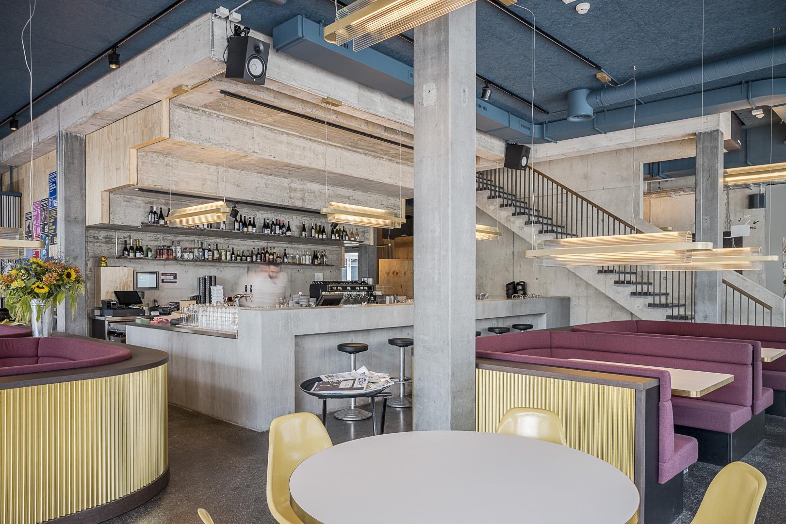 Bistro / Bar: Blick auf den Bistrobereich im Erdgeschoss, die Bar umgeben von rohem  Beton befindet sich unter der grossen Treppe, Einzeltische und gepolsterten Sitzbanknischen sorgen für eine angenehme und lockere Gruppierung der Gäste. © Burkhard & Lüthi