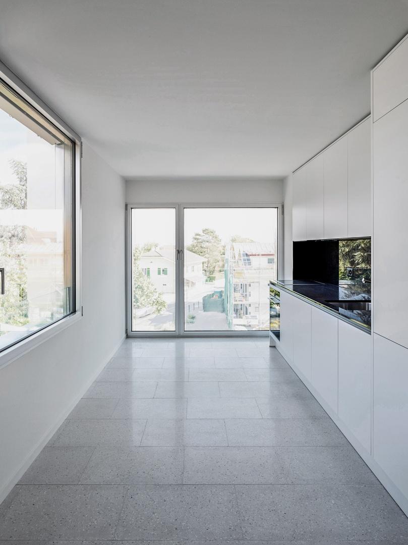 Die Materialität in jeder Wohnung verstärkt den Lichteinfall innerhalb des Hauses. Die ebenfalls  hellen Küchen sind mit einer Arbeitsplatte aus schwarzem Granit ausgestattet. © Collin Fontaine
