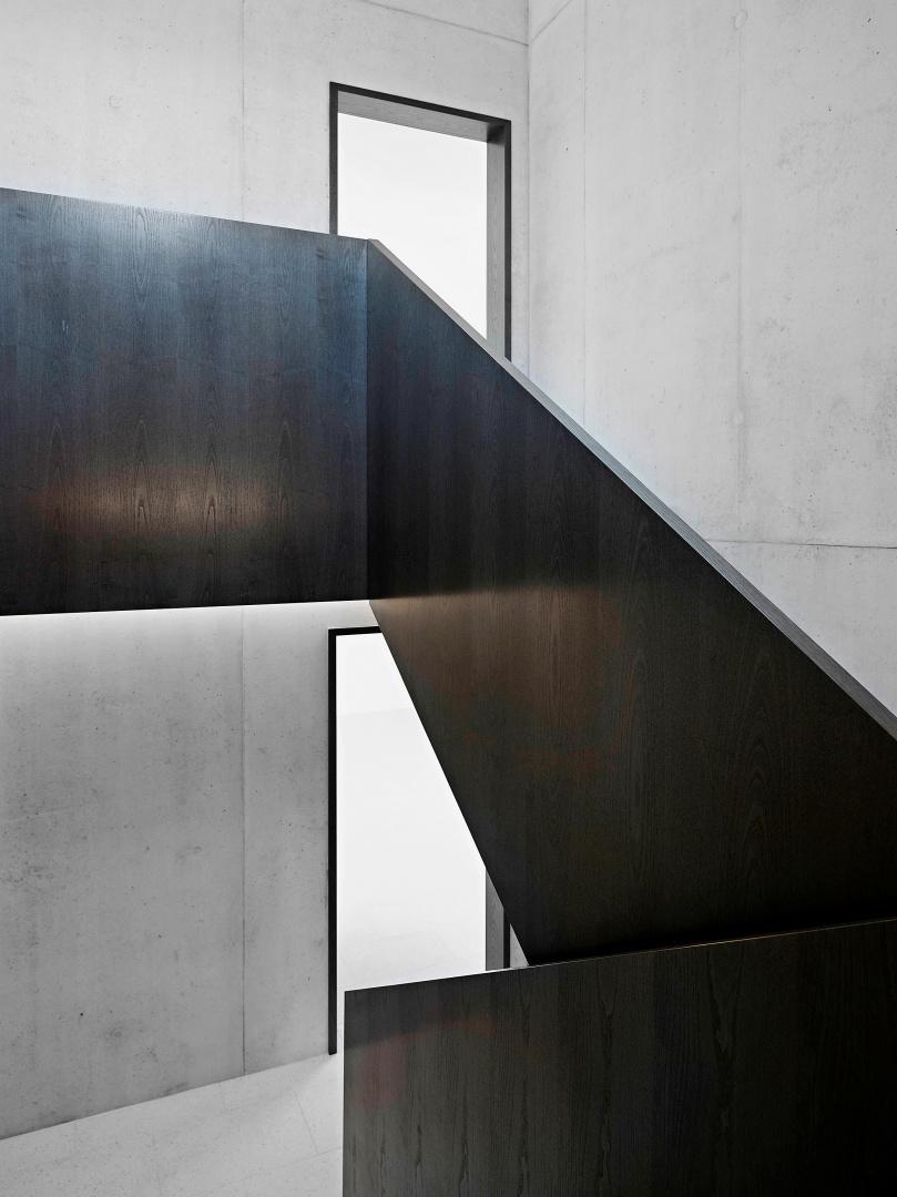 Alle Wände und Treppen der Gemeinschaftsräume sind aus Sichtbeton, während für die Türöffnungen und das Geländer dunkle Esche verwendet wurde. Wie  ein Band entwickelt es  sich nach oben und verbindet alle Etagen.  © Collin Fontaine