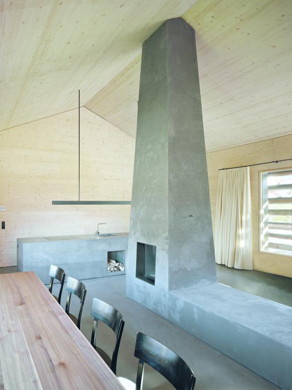 Der Wohnraum wird durch Küchenzeile und dem pyramidenförmige Kamin mit Sitzbank geprägt und zoniert.  © Ruedi Walti, Basel