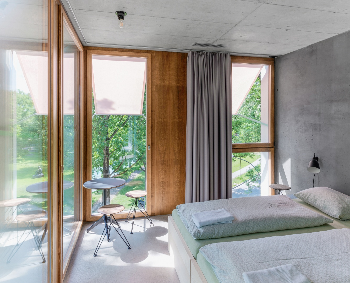 La chambre d'angle  pour les familles, au 1er étage  du nouveau dortoir. Avec sa  façade vitrée orientée sud-est et  les rives de l'Aar, elle ne diffère guère d'une chambre d'hôtel. © Adrian Scheidegger