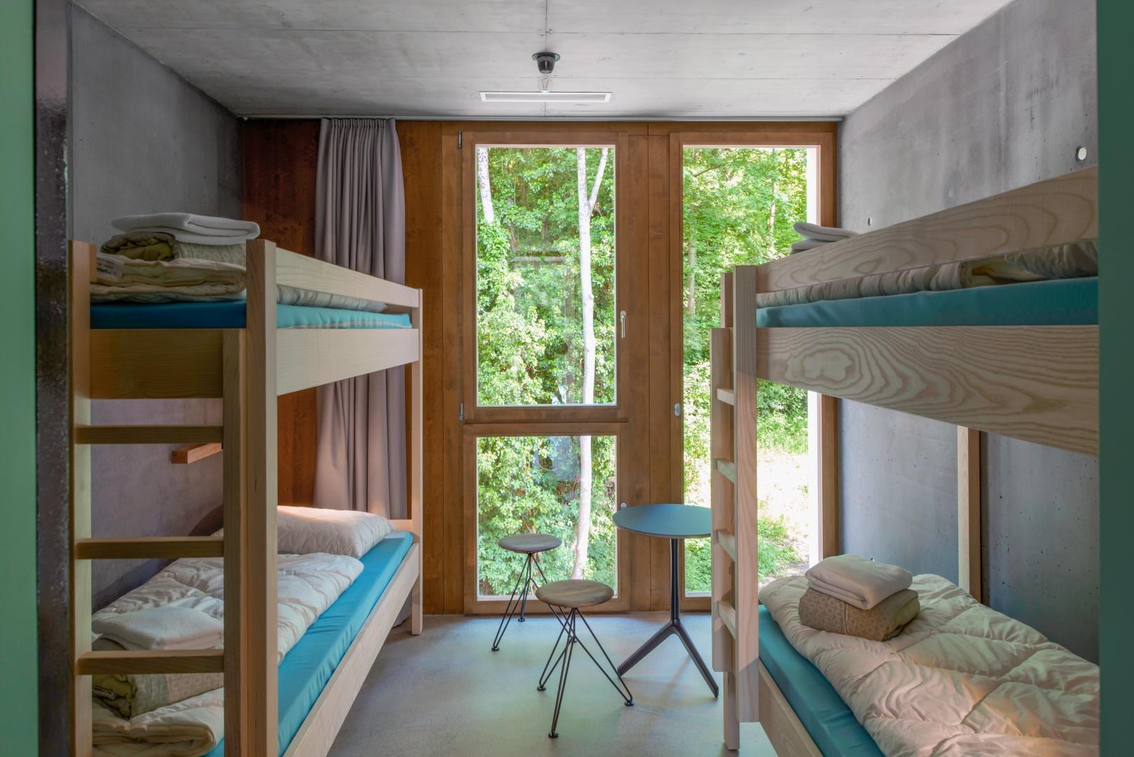 Vue sur la chambre à quatre lits  dans le nouveau dortoir: les deux  lits superposés bénéficient d'une vue sur la verdure qui entoure le Palais fédéral. © Adrian Scheidegger