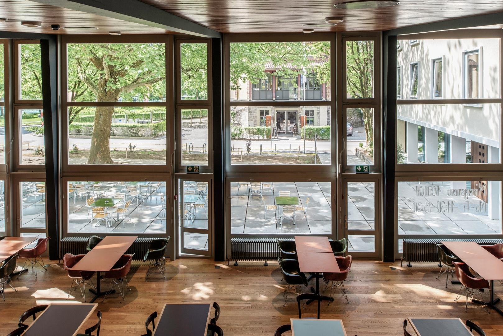 Blick vom Galeriegeschoss auf den grosszügigen Speisesaal (eingerichtet mit Möbeln von Horgen Glarus und Vitra), der mit seiner Glasfassade den Blick nach draussen auf das «Aussenzimmer» der Terrasse mit der mächtigen Platane freigibt. © Adrian Scheidegger