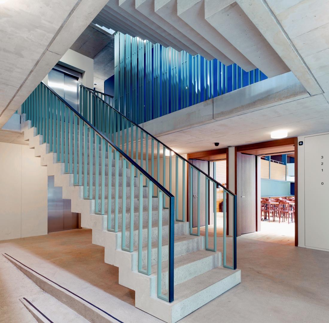 Das neue vorfabrizierte Treppenhaus im bestehen- den Dormitorium erstreckt sich über  vier Geschosse, akzentuiert mit einem Geländer in pastellfarbenem Grün. © Adrian Scheidegger