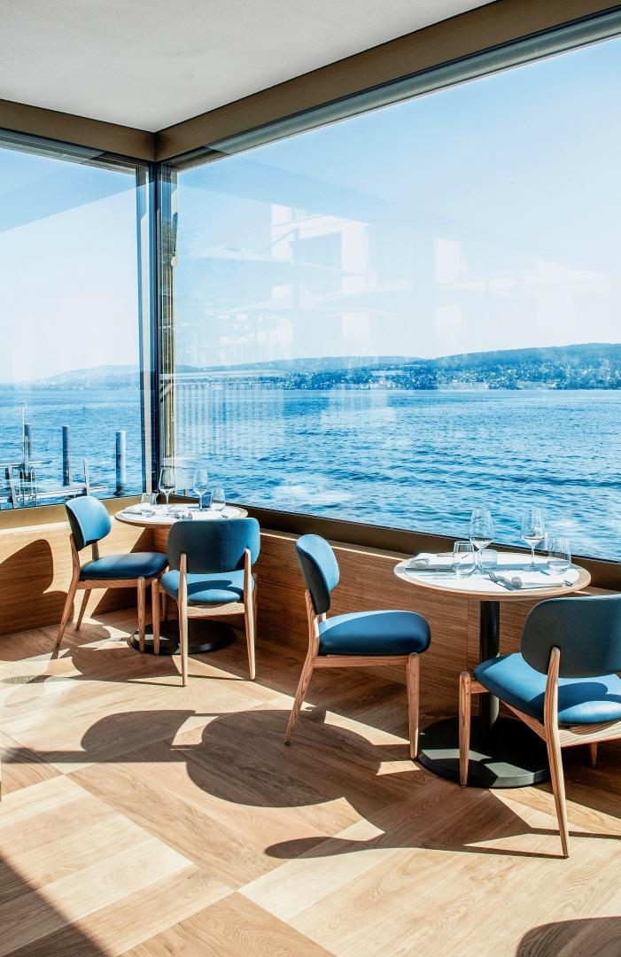 Au restaurant «The Boat House», entouré d'eau, les hôtes ont l'impression d'être sur un bâteau. Au loin, on voit uniquement la rive opposée, avec ses maisons et les collines, et tout au fond, la silhouette de la ville de Zurich. © Brady Williams