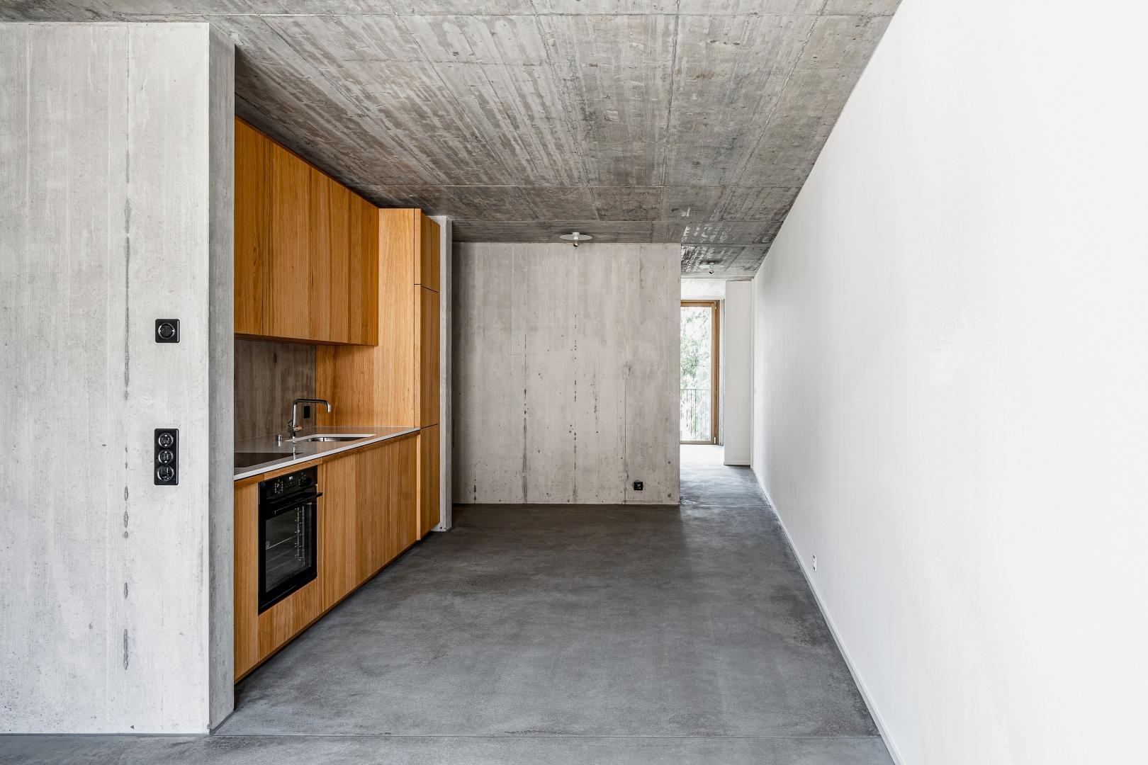 Die weiss verputzte Brandmauer zieht sich an der innenliegenden Küche vorbei von einer Fassadenseite zur anderen.  © Boris Haberthuer