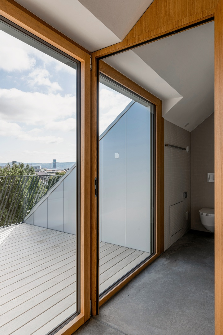 Blick aus der raumhohen Balkonverglasung auf  die obere Terrasse der Maisonnette-Wohnung  im Dach. © Boris Haberthuer