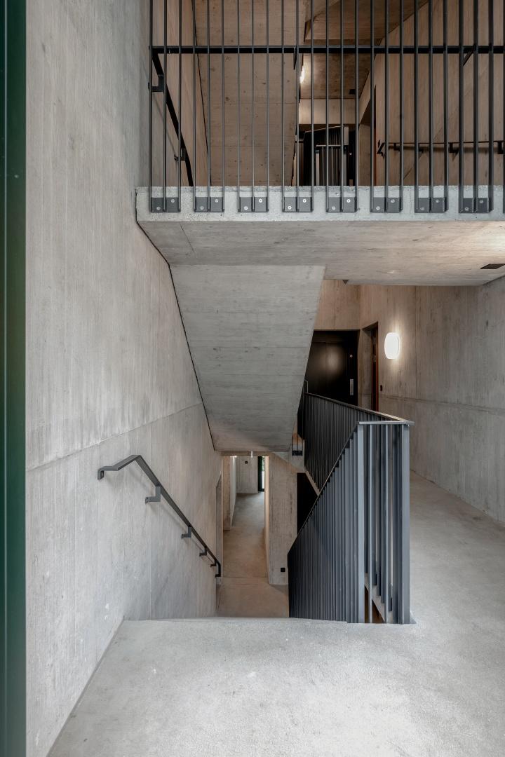 Das filigrane und durch die Gruppierung von jeweils drei Staketen doch  stabil wirkende Geländer ermöglicht Blickbeziehungen im Treppenhaus. © Boris Haberthuer