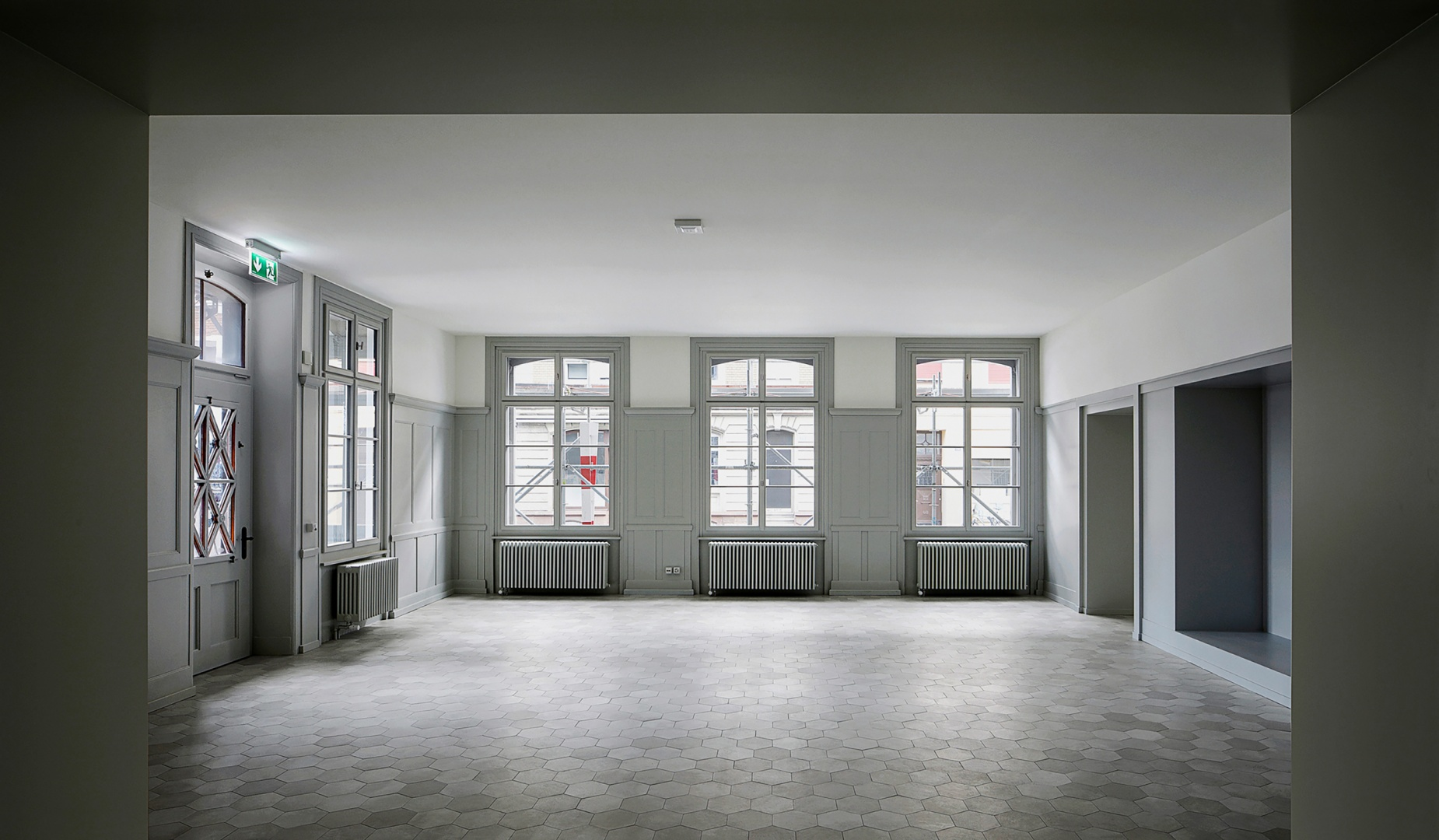 Blick in das Erdgeschoss des behutsam sanierten Altbaus,  das derzeit als Coworking-Space genutzt wird. Besonderheit sind die neu verlegten, grauen Sechseck-Fliesen aus Keramik. © Tom Bisig