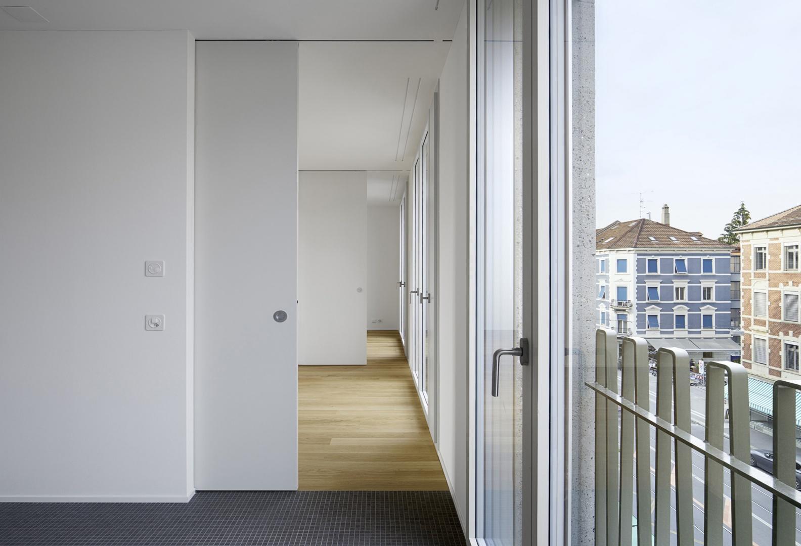 Blick von der Küche aus auf die Enfilade  der beiden weiteren Raumschichten. Raumhohe französische Fenster geben den Blick auf die belebte Klybeckstrasse frei. © Tom Bisig