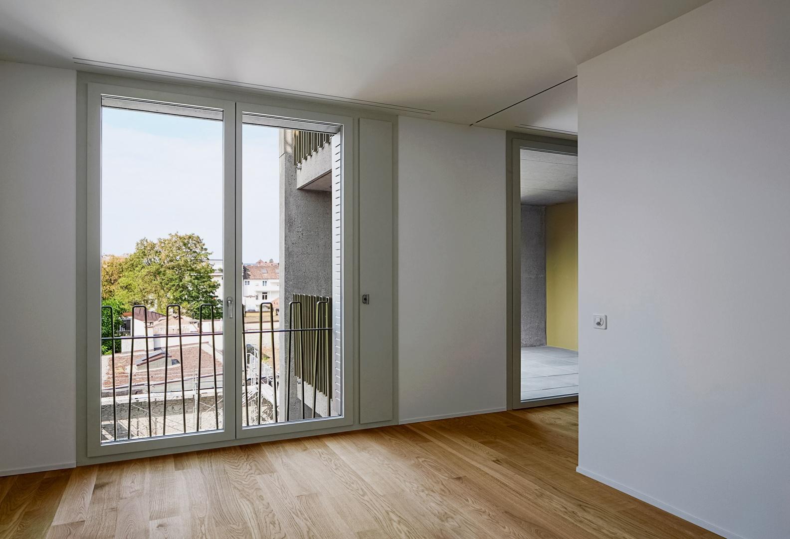 Blick auf die Hofseite: Das raumhohe französische Fenster wird seitlich  mit dem corbusianischen Lüftungsflügel ergänzt. Direkt dahinter befinden sich die zusammengeschobenen Faltschiebeläden. Rechts angeschnitten der Zugang zum gedeckten Balkon © Tom Bisig