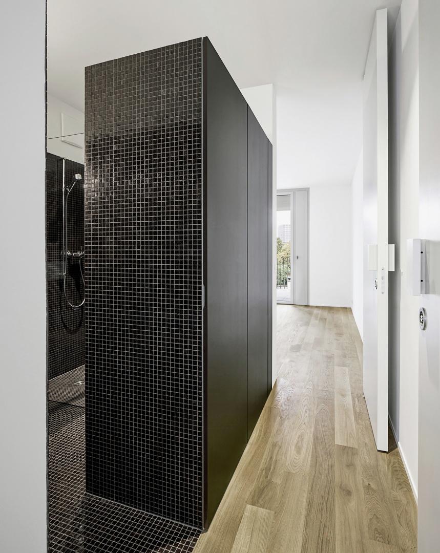 Die nördliche Schicht des Grundrisses mit der mittigen,  mit dunklen Mosaikfliesen ausgekleideten Nasszelle, die  ihn in zwei gleichwertige Räume teilt. Das Badezimmer ist  bei Bedarf von zwei Seiten mit einer Pivottür zu schliessen © Tom Bisig