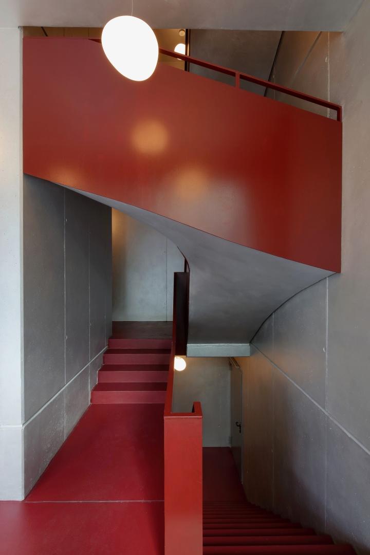 Treppenhaus Bernhardstrasse. Das Bordeauxrot der geschlossenen Treppenhausgeländer kontrastiert mit den silbernfarben angelegten Sichtbetonflächen. © Robert Mehl