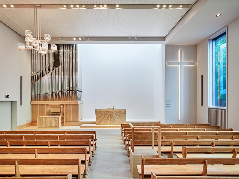 L'alignement symétrique des bancs  contraste avec la composition des éléments du chœur. Le pan de mur baigné dans la lumière zénithale qui tombe depuis l'élément haut ajouté sur le toit permet aussi la projection d'images. © Roger Frei