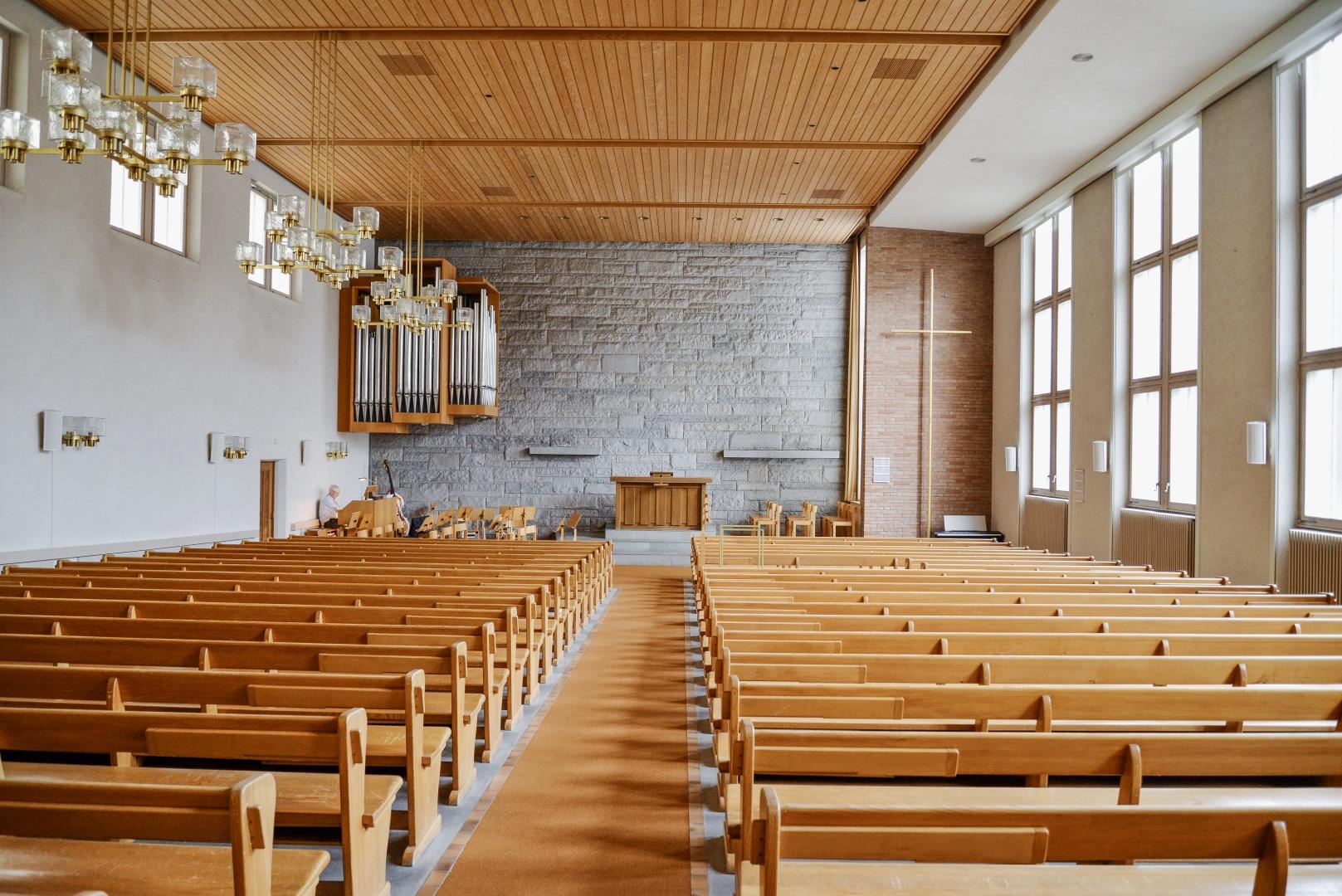 Parement en grès et en clinker, enduit  blanc, revêtement de plafond en bois laqué, tapis de sol: l'intérieur de l'église avant transformation était d'une matérialité très hétérogène contrastant avec l'actuelle matérialisation blanche et presque abstraite © Hinder Kalberer Architekten