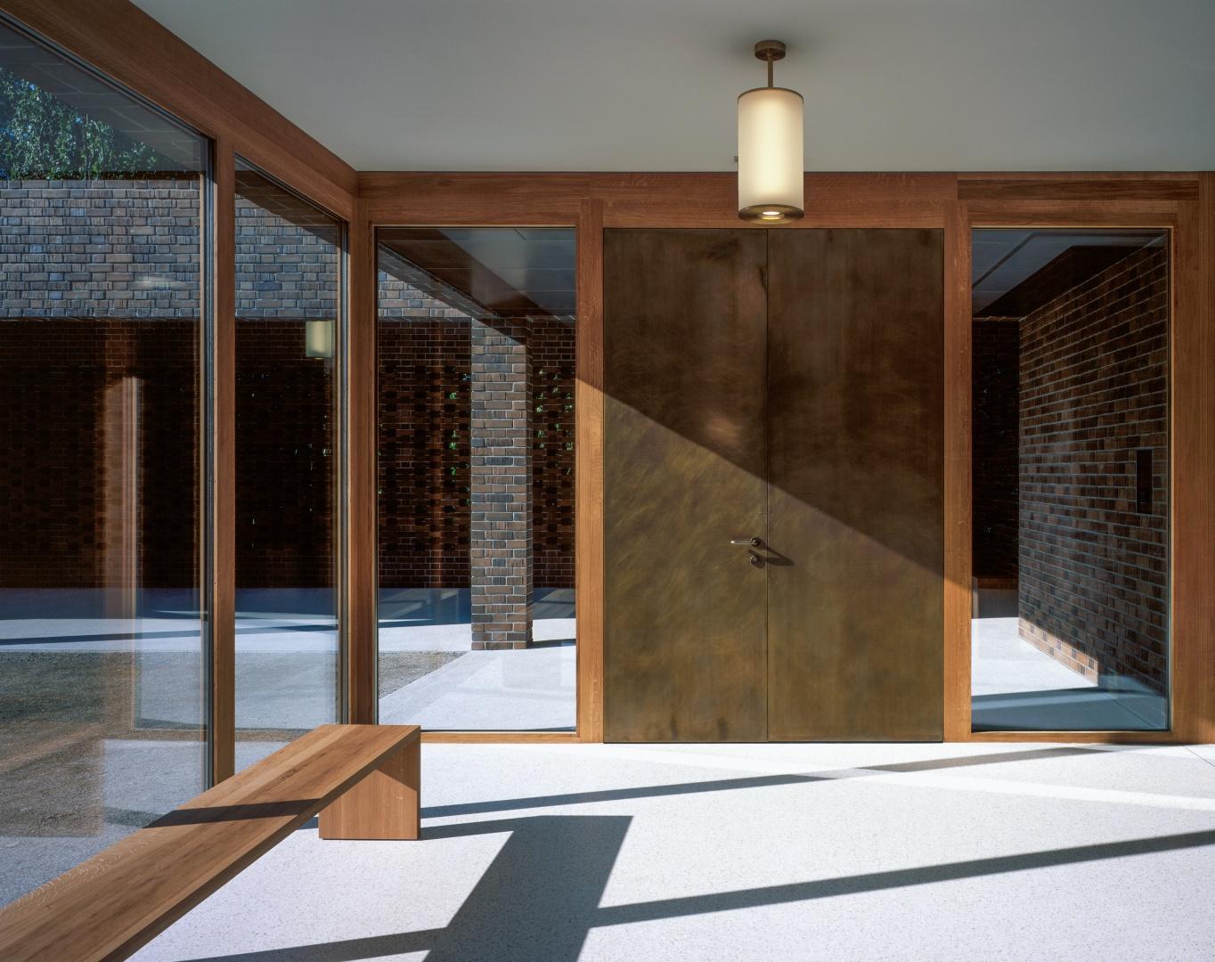 Die raumhohen Fenster erlauben den Blick zurück aus dem Eingangsbereich  in die Kolonnade. Das Thema des Übergangs  rückt ins Bewusstsein. © Hélène Binet