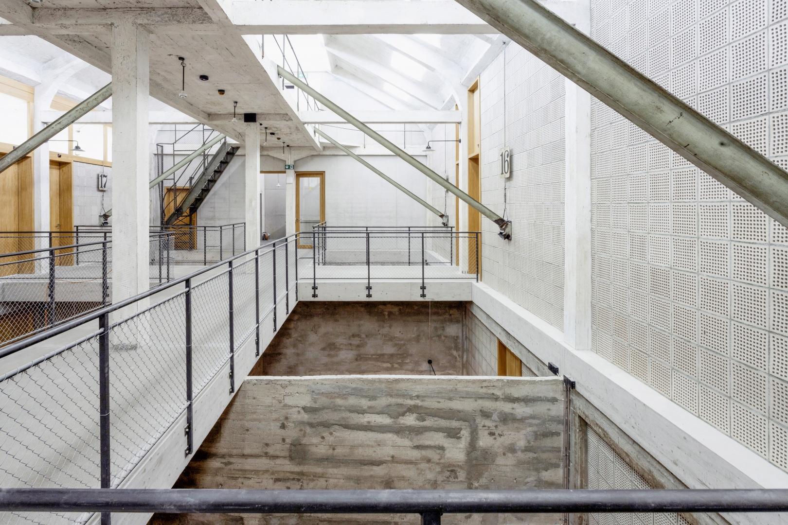 Die Mittelzone des Gebäudes wird von Licht durchströmt. Brücken führen über leere Silokammern in die Hostelzimmer oder Ateliers. © Lukas Schwabenbauer