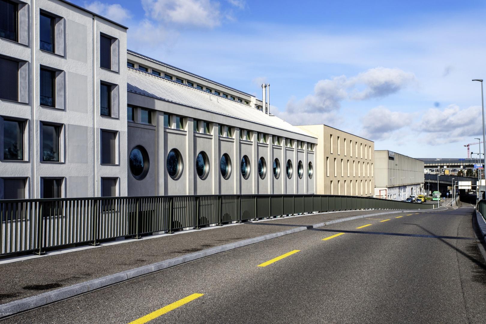 Das sanierte Gebäude mit  den neu eingesetzten Rund- fenstern. Im Hintergrund das angebaute Künstleratelier (Nullenergiehaus) von Degelo Architekten. © Lukas Schwabenbauer