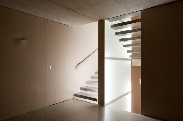Treppenhaus mit Leuchtkörper im Treppenauge. Licht wird über Bewegungsmelder immer dort geschaltet (auf- und abdämmend) wo sich jemand befindet. Dadurch folgt einem das Licht durchs Haus © Beat Bühler